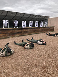 Men with guns laying on their back during a firearms training.