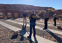 Law enforcement standing in front of targets at a gun range.