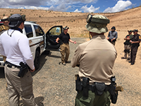 Law enforcement standing, talking next to a vehicle during a training exercise.